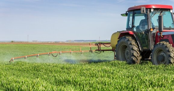 Tractor spraying a hay crop with preservatives